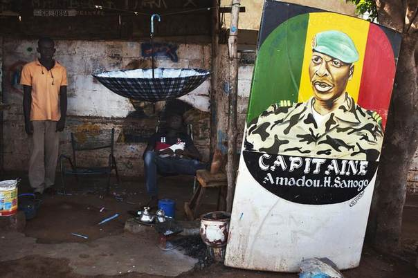 In this 2013 file photo, men sit next to a painting of the ex-junta leader Amadou Haya Sanogo in Bamako REUTERS/Joe Penney