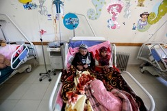 Boy and his sister who both suffer from cancer lie on a bed at a cancer treatment center in Sanaa
