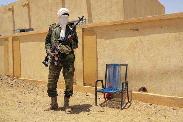 A fighter with the Tuareg separatist group MNLA (National Movement for the Liberation of Azawad) stands guard outside the local regional assembly, where members of the rebel group met with the Malian army, the UN mission in Mali and French army officers, in Kidal, June 23, 2013. REUTERS/Adama Diarra