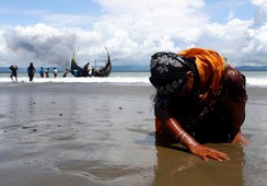 An exhausted Rohingya woman touches the shore after crossing the Bay of Bengal