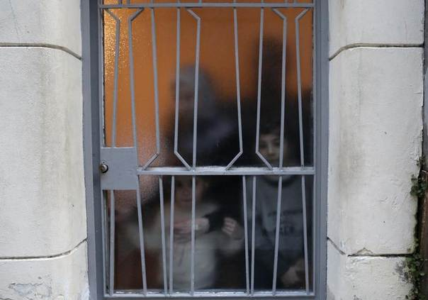 A Syrian refugee family are seen through a door in Athens. Picture taken February 7, 2013. REUTERS/John Kolesidis