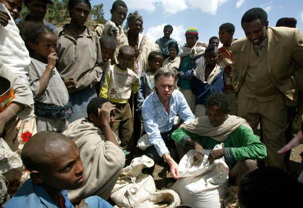 Irish rock star Bob Geldof (C) helps people at a feeding centre in Lalibela, 700km from the capital Addis Ababa, Ethiopia in May 2003. REUTERS/Antony Njuguna
