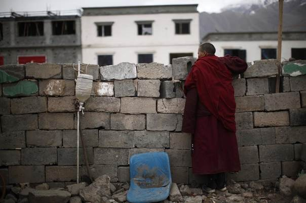 A Tibetan ethnic nun watches reconstruction at an area affected by the 2010 earthquake in Yushu, Qinghai province, April 22, 2012. REUTERS/Carlos Barria