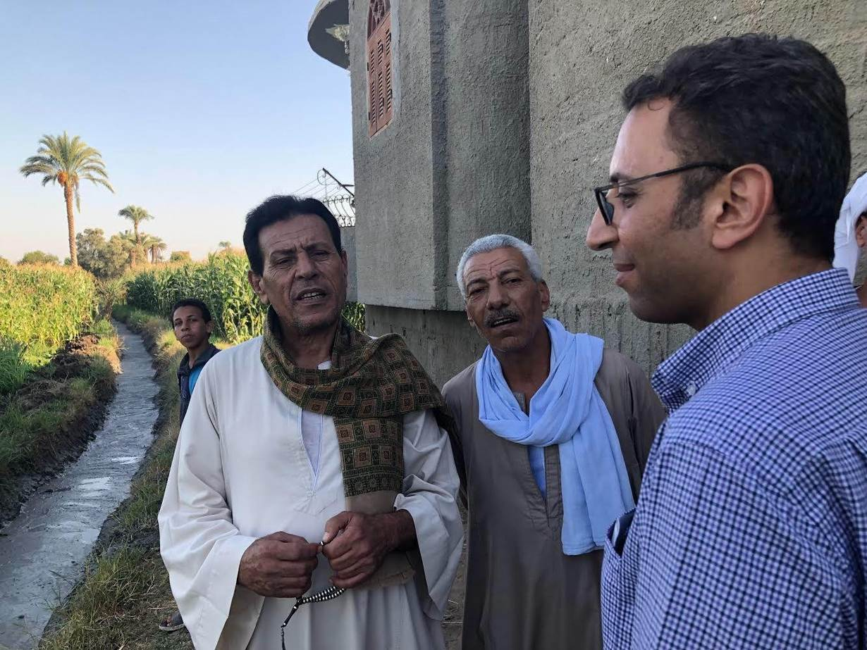 Hatem Samir (left), an agricultural officer, speaks with farmers near a modern agricultural canal in the Upper Egyptian city of Assuit, September 13, 2019. Thomson Reuters Foundation/Menna A. Farouk