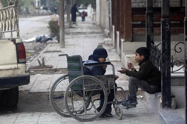 A child on a wheelchair rests on a street in Eastern Ghouta in Damascus January 3, 2014. REUTERS/Diaa Al-Din