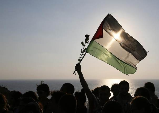 Protesters wave a Palestinian flag and flowers during a sit-in protest against Israel's military action in Gaza, on the Mediterranean coast at Rawshe rock in Beirut July 22, 2014. REUTERS/Jamal Saidi