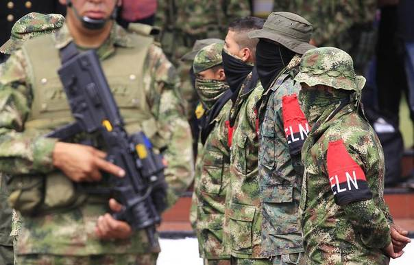 Defected members (with armbands) of Colombian guerrilla group ELN fall in at a military base during their surrender and the handover of their weapons, in Cali, Colombia, July 16, 2013. REUTERS/Jaime Saldarriaga