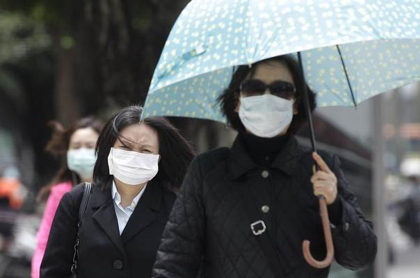 Pedestrians wearing medical masks walk on the street outside National Taiwan University Hospital in Taipei, Taiwan, April 26, 2013. REUTERS/Pichi Chuang