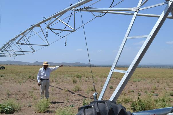 A farmer stands with an irrigation rig in Kenya. THOMSON REUTERS FOUNDATION/Isaiah Esipisu