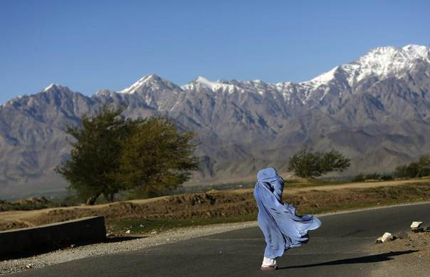 An Afghan woman in a burqa walks along a road on a windy day on the outskirts of Kabul, Afghanistan,April 16, 2013. REUTERS/Mohammad Ismail