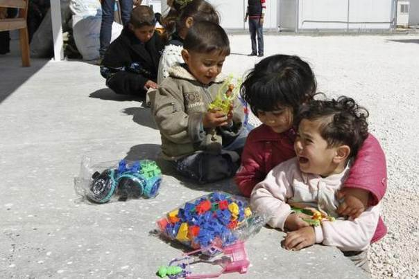 Syrian refugee children play with toys given by Members of the UAE Red Crescent after their arrival at the new Mrajeeb Al Fhood refugee camp 20 km east of the city of Zarqa, April 10, 2013. REUTERS/Muhammad Hamed