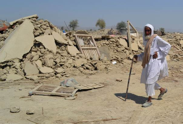 A survivor of an earthquake walks near the rubble of a mud house after it collapsed following the quake in the town of Awaran, in the southwestern Pakistani province of Baluchistan, on September 25, 2013. REUTERS/Naseer Ahmed