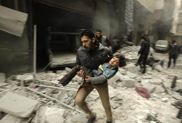 A man runs as he carries a child who survived from what activists say was an airstrike by forces loyal to Syrian President Bashar al-Assad, at al-Ferdaws in Aleppo January 21, 2014. REUTERS/Ammar Abdullah