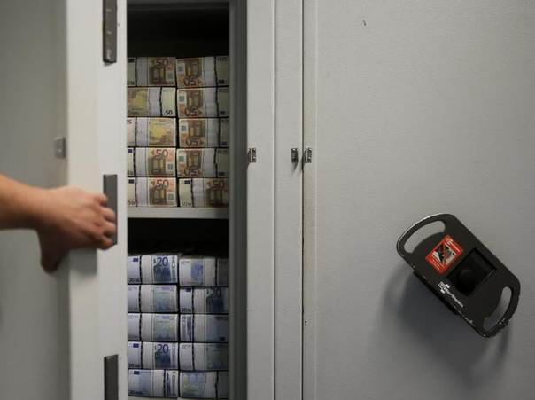 An employee of GSA Austria (Money Service Austria) opens a safe containing bundles of 50 and 20 euro banknotes at the company's headquarters in Vienna July 22, 2013. The GSA delivers new and collects old currency for the Austrian National Bank. REUTERS/Leonhard Foeger