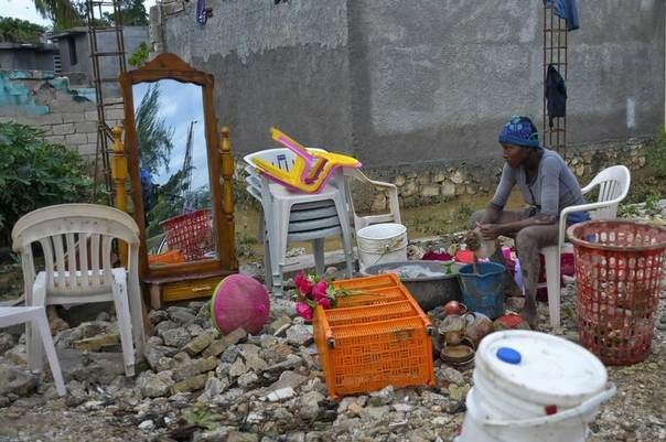 A Haitian woman whose house was flooded by Tropical Storm Isaac sits with the items she was able to salvage, in an area outside the capital Port-au-Prince August 26, 2012. REUTERS/Swoan Parker