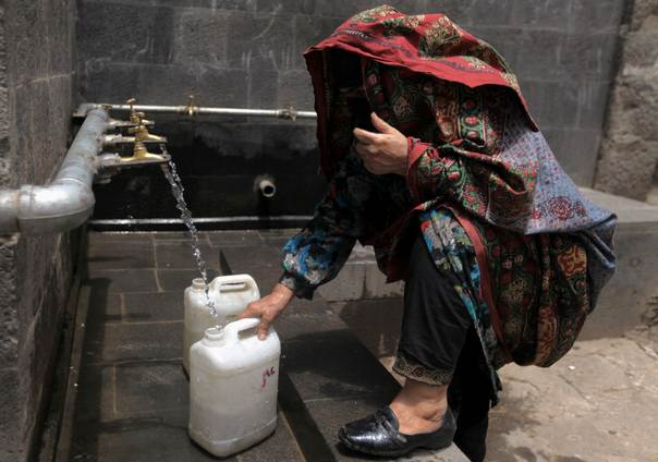 A woman wearing a traditional outfit fills a water container in Sanaa, Yemen, on July 3, 2013. REUTERS/Mohamed al-Sayaghi