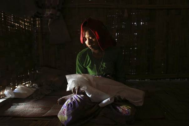 Gorima Khatu holds the covered body of her three-month-old daughter Asoma Khatu, who just died of fever and diarrhoea, in their room at the Kyein Ni Pyin camp for internally displaced people in Pauk Taw, Rakhine state, April 23, 2014 REUTERS/Minzayar