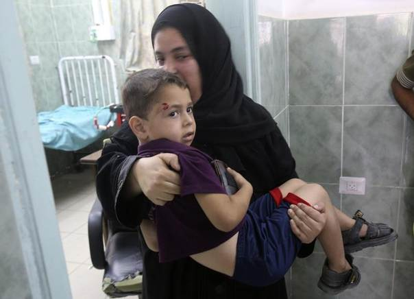 A Palestinian woman carries a boy, whom medics said was wounded by Israeli shelling, at a hospital in Rafah in the southern Gaza Strip August 1, 2014. REUTERS/Ibraheem Abu Mustafa
