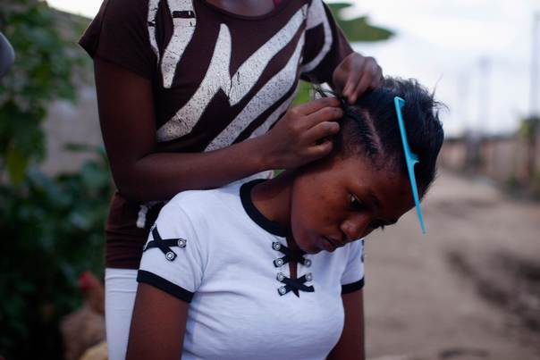A girl braids her friend's hair in Douala, Cameroon, November 3, 2013. REUTERS/Joe Penney
