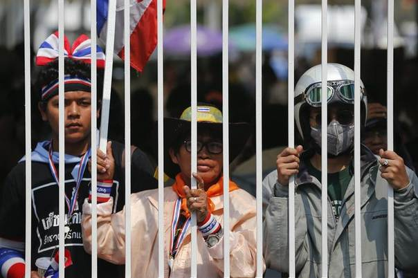 Anti-government protesters look though the gates of a polling station their group closed in Bangkok, Thailand, January 26, 2014. REUTERS/Damir Sagolj