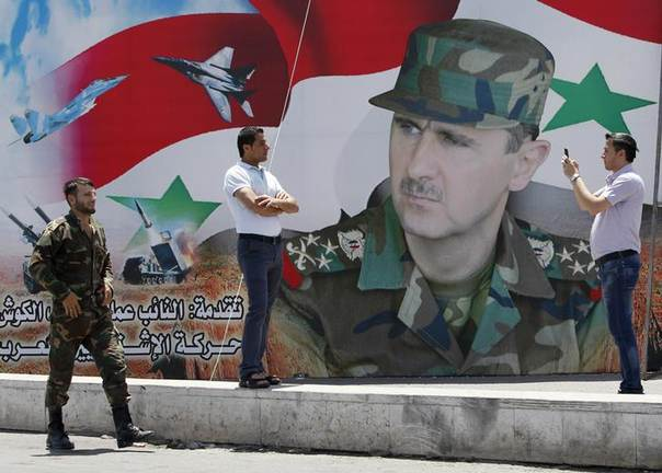 A man takes a photo of his friend in front of a poster of Syria's President Bashar al-Assad at Umayyad Square in Damascus May 16, 2014 REUTERS/Khaled al-Hariri