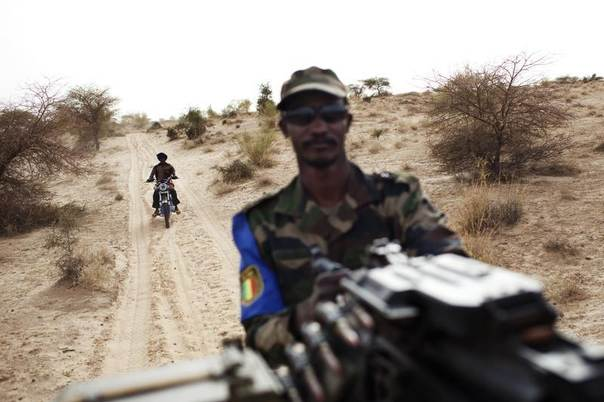 A Malian soldier holds a machine gun mounted on a pick-up truck during a military escort outside Timbuktu, Mali, July 27, 2013. REUTERS/Joe Penney