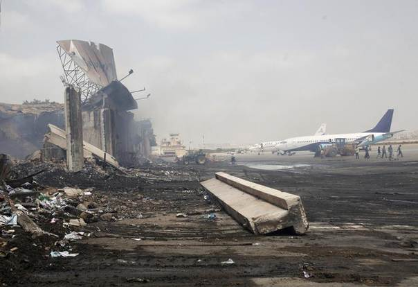 Planes are seen near a section of a damaged building (L) at Jinnah International Airport, after Sunday's attack by Taliban militants, in Karachi June 10, 2014 REUTERS/Athar Hussain