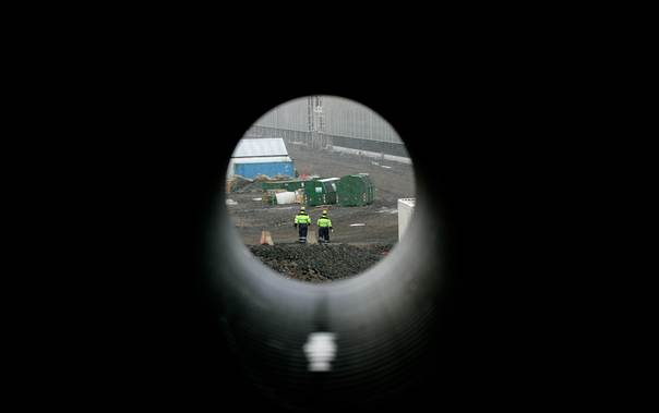 Workers are seen through a pipe as they walk near an Alcoa Fjardaal aluminium smelter potline, eastern Iceland, on April 16, 2007. To match feature ICELAND-SMELTERS/ REUTERS/Stoyan Nenov