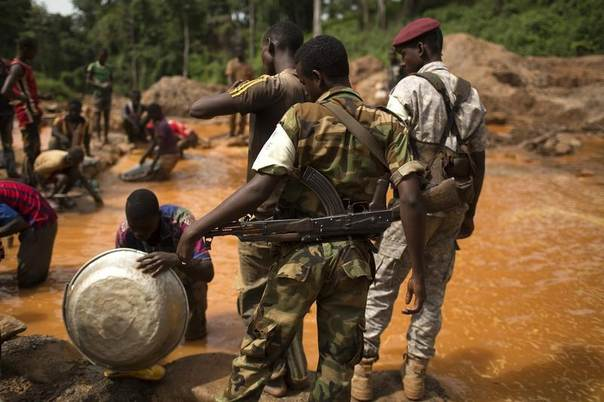 Former Seleka soldiers look at prospectors washing extracted soil and small rocks as they pan for gold near the open-pit at the Ndassima gold mine near Djoubissi, north of Bambari, Central African Republic, May 9, 2014. REUTERS/Siegfried Modola