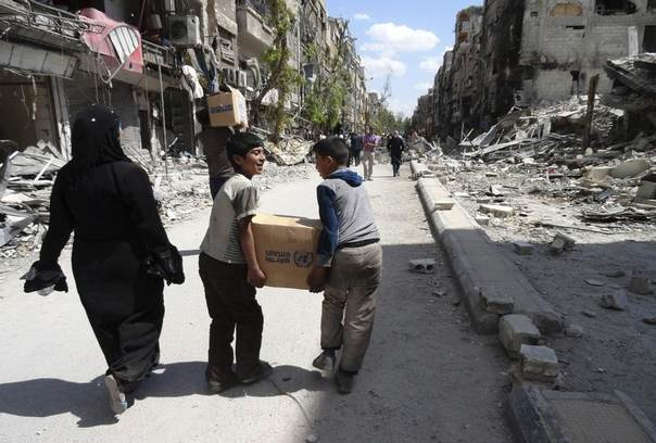 Palestinians from the besieged al-Yarmouk camp carry food aid they received from UNRWA at the entrance of the camp in Rama street, south of Damascus, Syria, May 1, 2014. REUTERS/Rame Alsayed