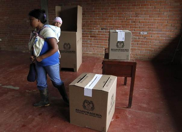 A woman with her child leaves after casting her vote during a congressional election in Toribio in Cauca province, Colombia, March 9, 2014. REUTERS/Jaime Saldarriaga