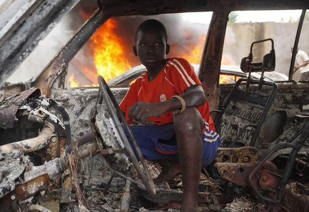 A Christian youth squats inside a burnt out car in Bangui December 10, 2013 REUTERS/Emmanuel Braun
