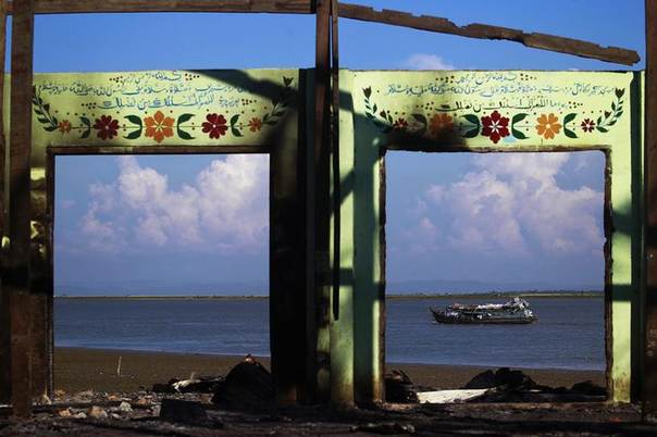 In this 2012 file photo, a boat is framed by the ruins of a destroyed mosque in a part of Pauktaw township, Myanmar that was burned in recent violence REUTERS/Soe Zeya Tun