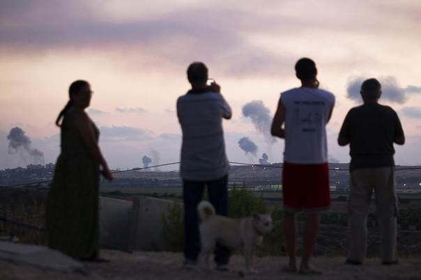 Israelis watch as smoke rises after air strikes across the border in northern Gaza July 8, 2014. REUTERS/Amir Cohen