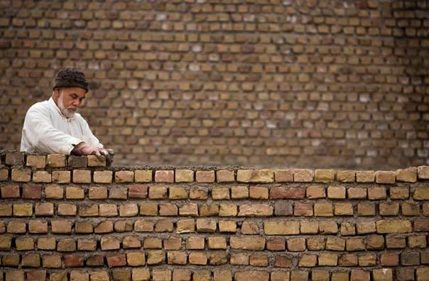 An Afghan builder rebuilds a wall of a house in Herat, on Nov. 1, 2009. REUTERS/Morteza Nikoubazl