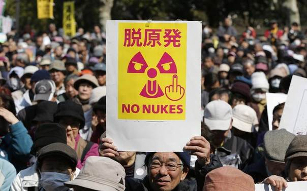 An anti-nuclear protester holds a banner saying