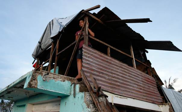 A typhoon survivor looks out from her damaged house that has become a makeshift shelter in Tacloban city in central Philippines, on Dec. 15, 2013. REUTERS/Erik De Castro