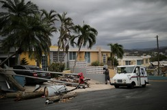 A mail man for the U.S. Postal Service delivers the mail at an area damaged by Hurricane Maria in Puerto Rico