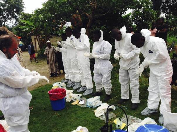 Volunteers prepare to remove the bodies of people who were suspected of contracting Ebola and died in the community in the village of Pendebu, north of Kenema July 18, 2014. REUTERS/WHO/Tarik Jasarevic/Handout via Reuters