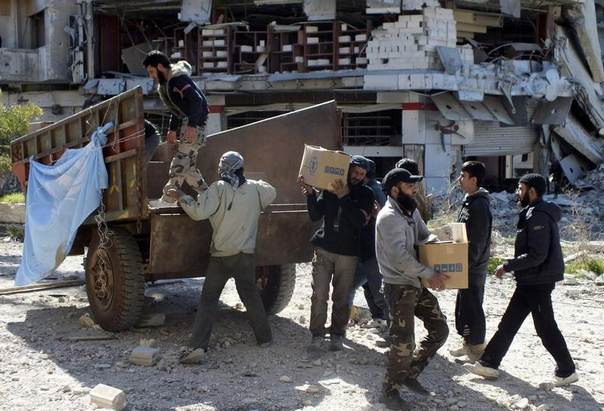 Men unload boxes of U.N. humanitarian aid at a besieged area of Homs, Syria, February 12, 2014. REUTERS/Yazan Homsy