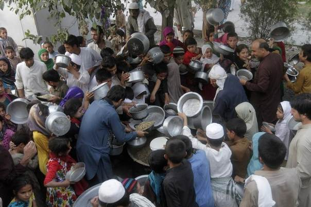Afghans receive food charity during the Muslim holy month of Ramadan in Jalalabad city July 8, 2014. REUTERS/Parwiz