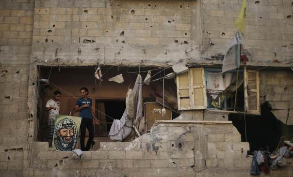 Palestinians stand next to a picture depicting late Palestinian leader Yasser Arafat as they inspect a house which police said was damaged in an Israeli air strike in Gaza City July 10, 2014.  REUTERS/Mohammed Salem