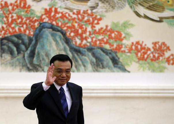 China's Premier Li Keqiang waves as he arrives for a news conference, after the closing ceremony of the Chinese National People's Congress at the Great Hall of the People, in Beijing, March 13, 2014. REUTERS/Kim Kyung-Hoon