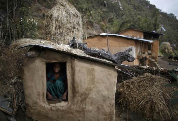 Uttara Saud, 14, sits inside a Chaupadi shed in the hills of Legudsen village in Achham District in western Nepal February 16, 2014. REUTERS/Navesh Chitrakar