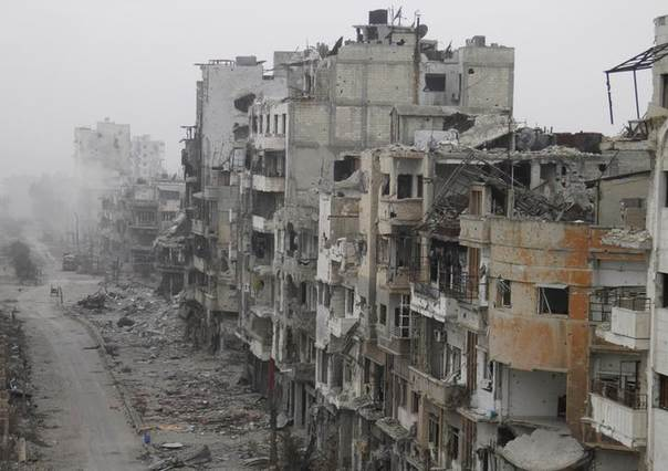 Smoke rises from buildings after what activists said was shelling from forces loyal to Syria's President Bashar al-Assad in the besieged area of Homs January 15, 2014. REUTERS/Thaer Al Khalidiya