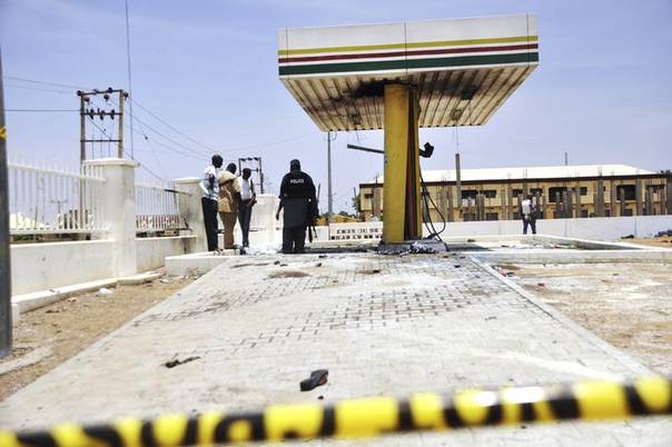 Members of the bomb squad inspect a Nigerian National Petrolium Corporation (NNPC) petrol station after a female suicide bomber blew herself in the city of Kano July 28, 2014.