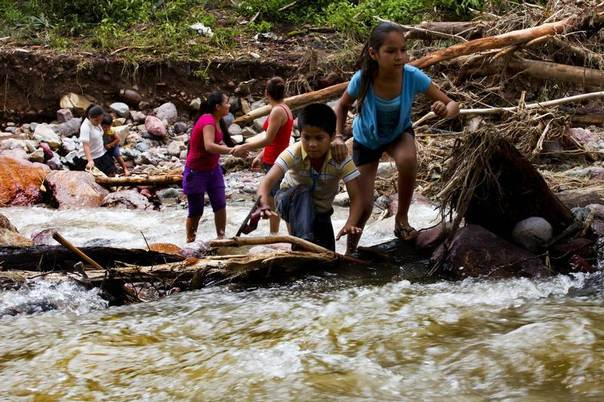 Children cross a river in the mountain range of Zihuatanejo in Guerrero state, which has been the hardest hit by heavy rains unleashed by Hurricane Manuel in Mexico last week, Sept. 22, 2013. REUTERS/Jacobo Garcia