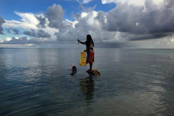 Binata Pinata stands on a rock holding a fish her husband just caught off Bikeman islet, located off South Tarawa in the central Pacific island nation of Kiribati, which is threatened by sea-level rise, May 25, 2013. REUTERS/David Gray