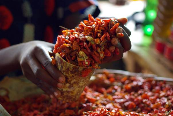 A vendor measures a cup of dried chilli peppers at a food market in Sierra Leone's capital Freetown, on March 13, 2008. REUTERS/Katrina Manson
