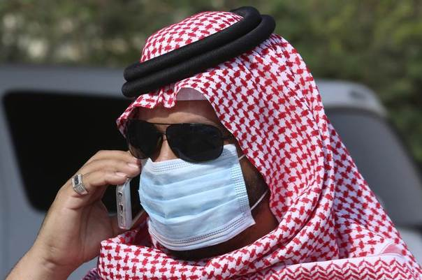 A man with mask speaks on his mobile phone in Jeddah May 29, 2014. REUTERS/Mohamed Alhwaity